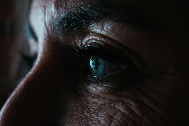 Nahaufnahme des Auges einer Frau im Halbdunkel.
