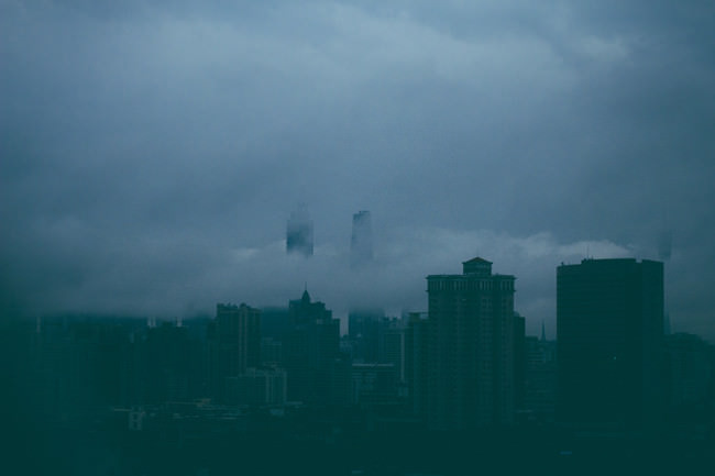 Hochhäuser einer Großstadt, die in tiefhängenden Wolken stehen.