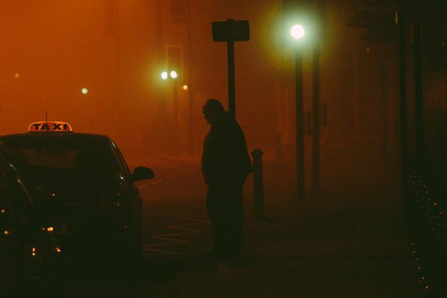 Silhouette eines Mannes, der in diesigem Licht neben einem Taxi am Straßenrand steht.