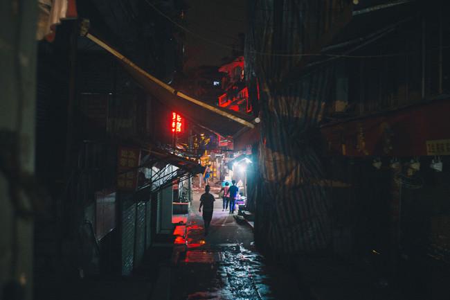 Menschen in einer verbauten Gasse einer asiatischen Stadt.