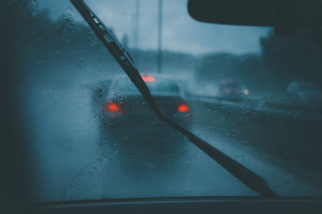 Blick durch eine nasse Autoscheibe hinaus auf Rücklichter anderer Autos.