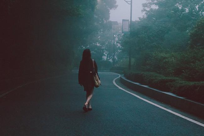 Eine Frau läuft auf einer leeren Straße in diesigem Wetter.