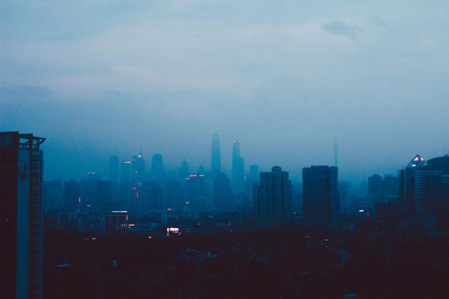 Eine diesige asiatische Großstadt in Blautönen.