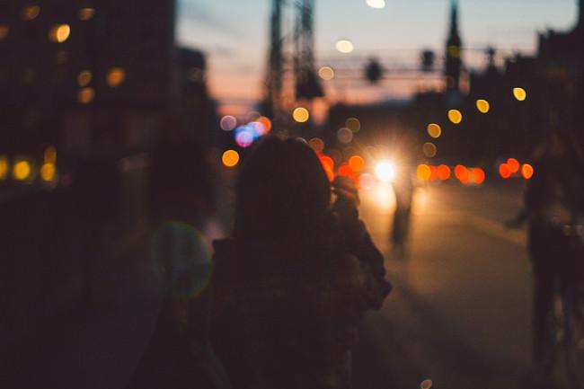 Silhouette einer Person in einem Bokehmeer aus Stadtlichtern.