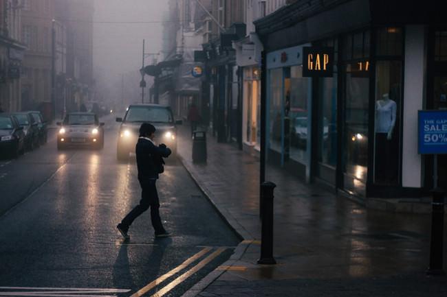 Eine Person überquert eine nasse Straße.