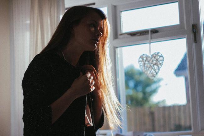 Eine Frau knöpft sich vor einem Fenster eine Bluse zu.