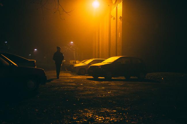 Eine Person geht im Dunkel über einen nebligen Parkplatz.