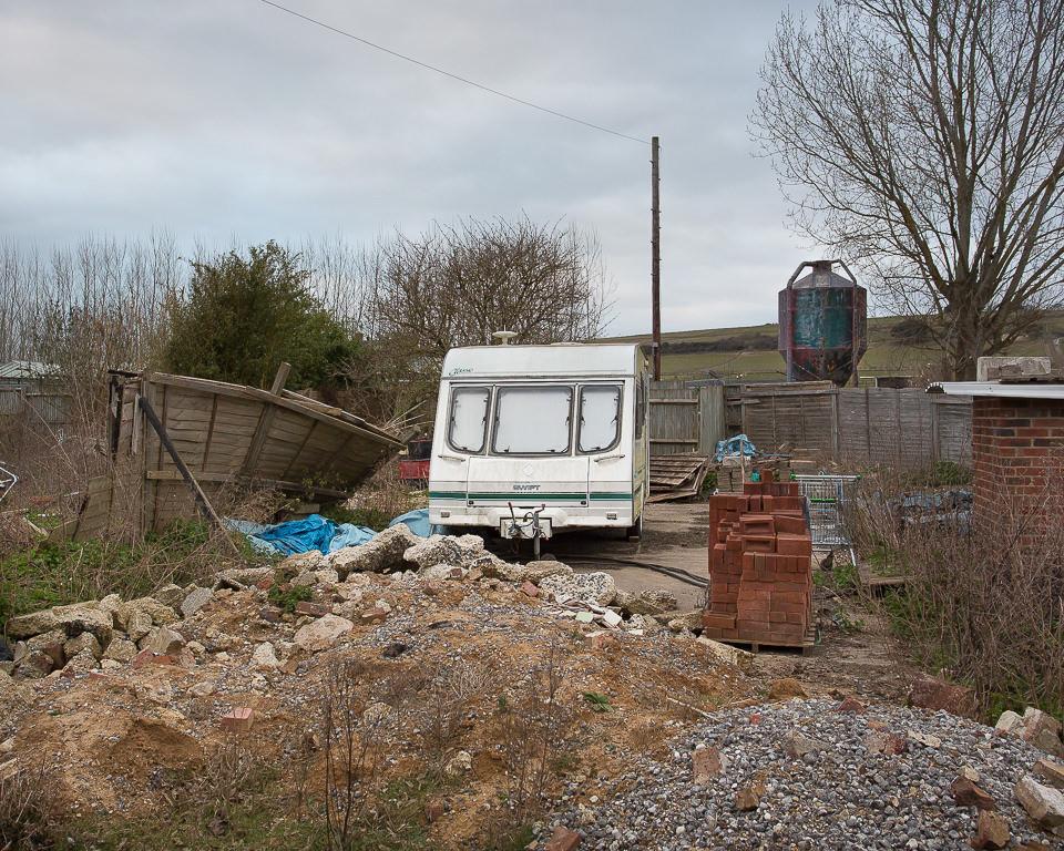 Ein alter wohnwagen steht in einem ungepflagten Hinterhof.