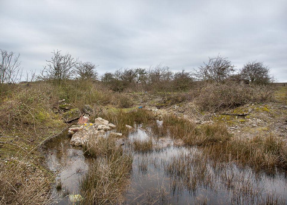 Ein vollgemüllter und Sumpf in karger Landschaft.