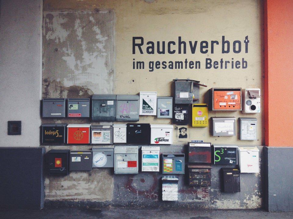 """Eine Wand mit sehr vielen unterschiedlichen Briefkästen und dem Schriftzug """"Rauchverbot im gesamten Betrieb""""."""