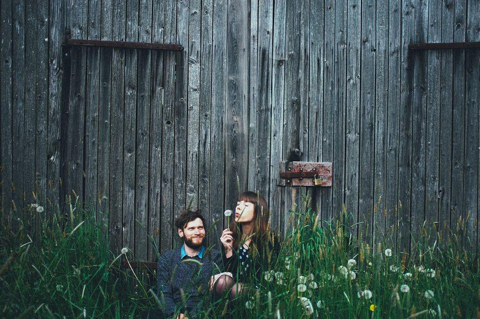 Eine Frau und ein Mann hocken im Gras vor einer Scheune, sie pustet eine Pusteblume in die Luft.