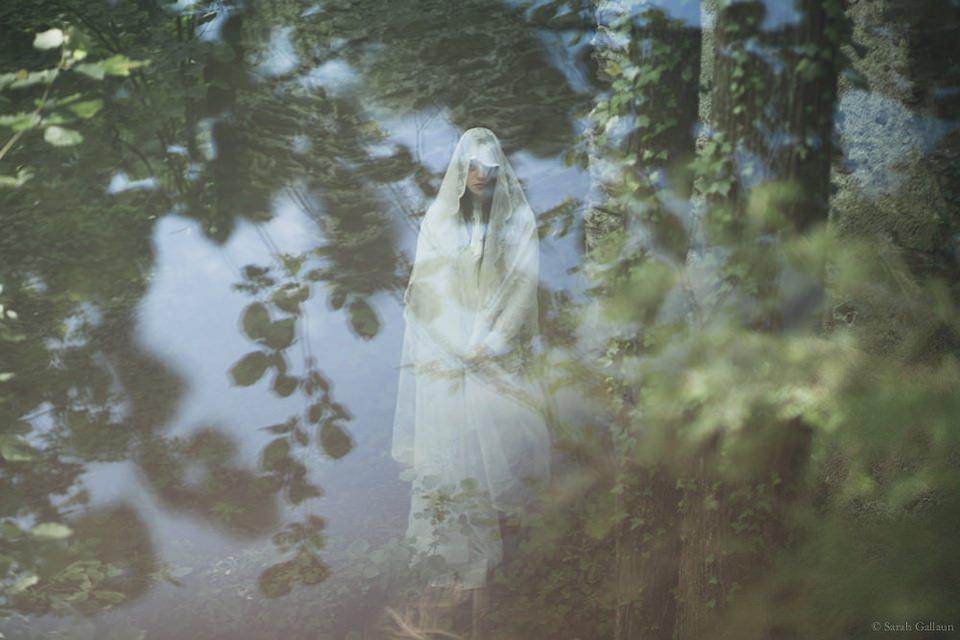 Eine Frau in weißem Kleid im Wald, überlagert von Spiegelungen.