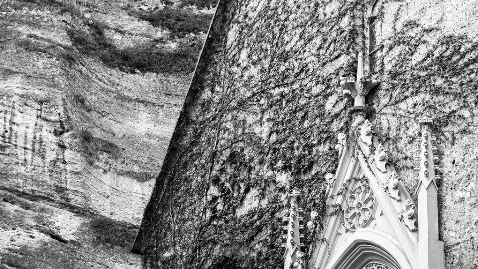 Efeubewachsene Wand einer Kirche vor einer natürlichen Steinwand.
