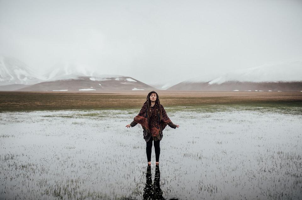 Frau in einem See stehend vor Bergkulisse