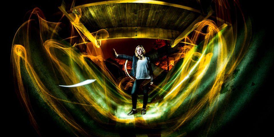 Frau steht in gelben und grünen Lichtern.