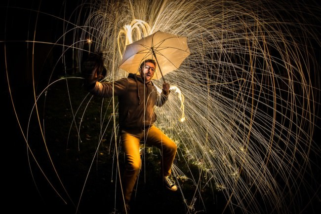 Ein Mann hält sich einen funkensprühenden Schirm aufgespannt über den Kopf.