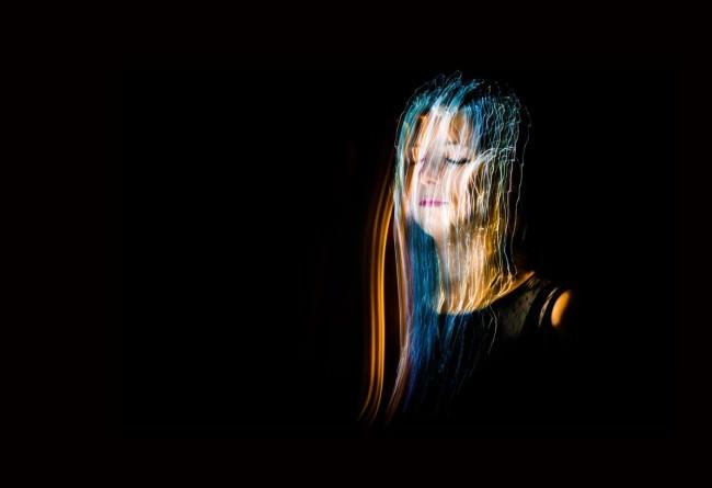 Eine Frau mit einem Schleier aus bunten Lichtern vorm Gesicht.