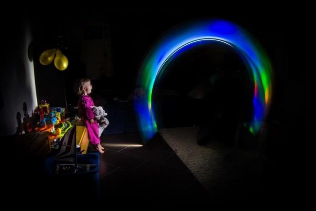 Ein kleines Mädchen steht staunend vor einem bunten Lichtbogen in einem dunklen Zimmer.