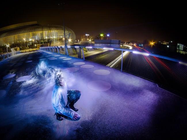 Frau auf einer violett beleuchteten Brücke.