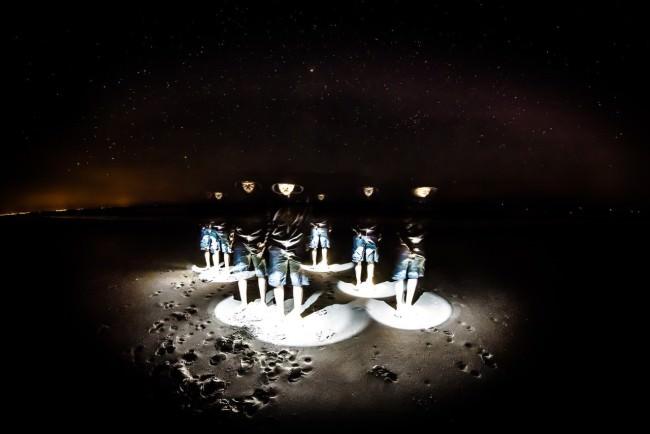 Mehrfachbelichtung eines Mannes in einem leuchten Kreis in Dunkelheit am Strand.