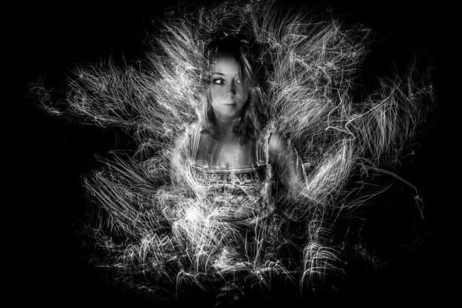 Frau im Dunkeln von Lichtgekritzel umgeben.