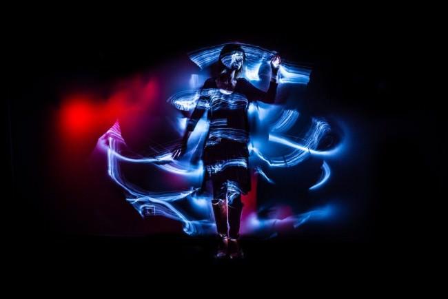 Eine Frau im Dunkeln von bunten Lichtschlieren umgeben.