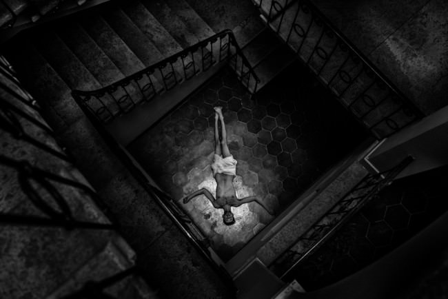 Ein Mann liegt am Boden eines Treppenhauses