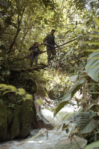 Zwei bewaffnete Menschen gehen über eine schmale Brücke