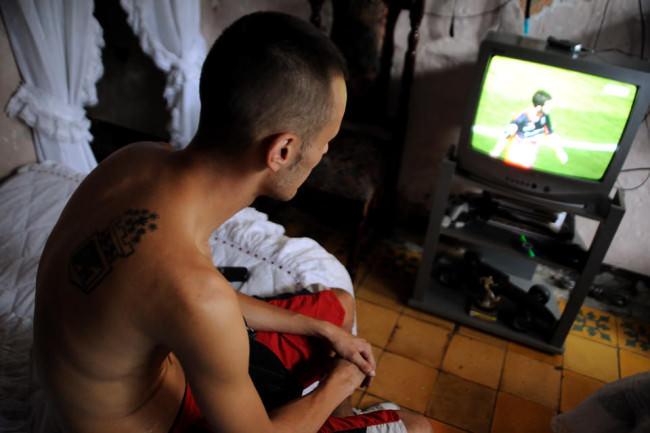 Mann mit Tattoos sieht Fernsehen