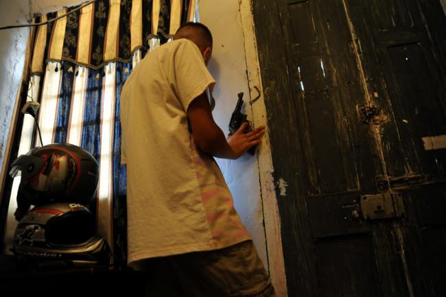 Mann mit Waffe an einer Tür
