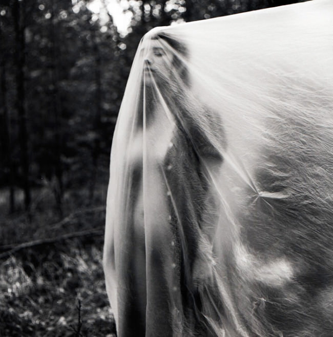 Eine Frau steht im Wald und hat die Augen geschlossen.