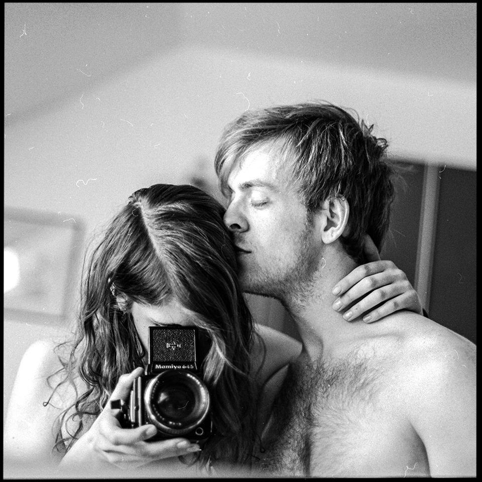 Eine Frau schaut in den Spiegel und macht ein Selbsportrait mit ihrem Freund.
