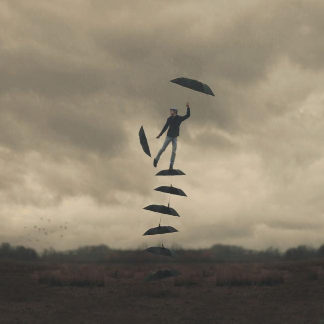Ein Mann balanciert auf Regenschirmen