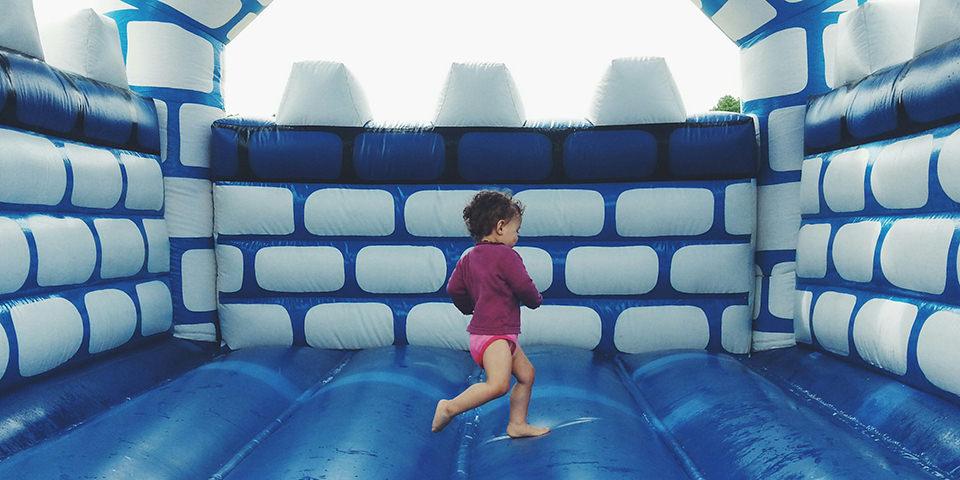 Kind auf einer blauen Hüpfburg