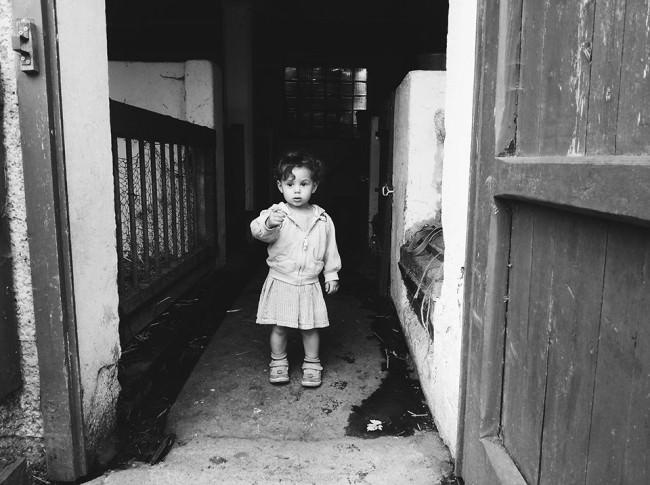 Kleinkind steht in der Tür eines Stalls
