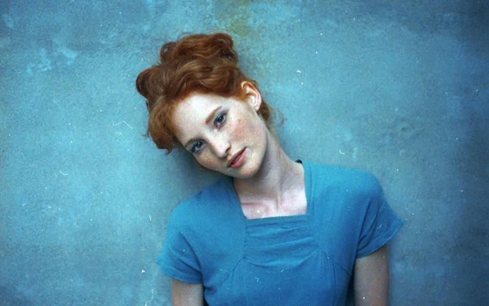 Eine rothaarige Frau steht vor einer blauen Wand und neigt den Kopf.