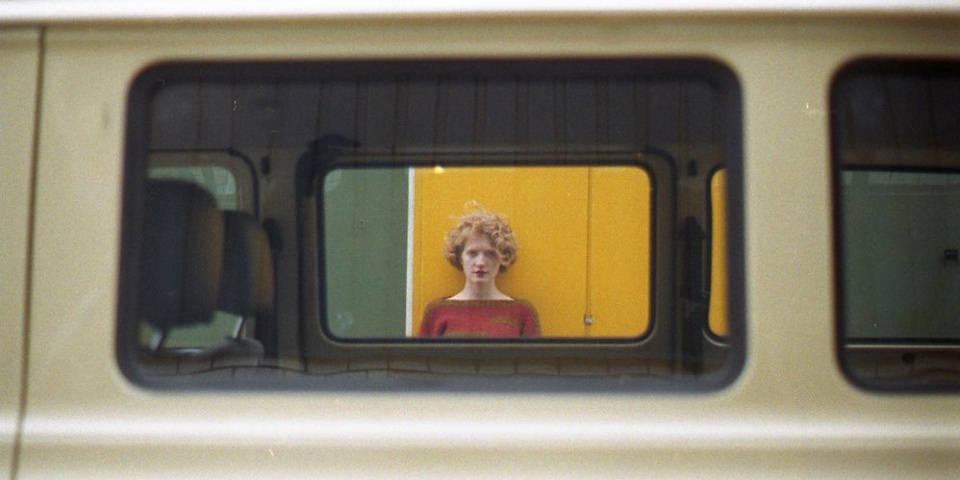Eine blonde Frau ist durch ein Autofenster sichtbar.