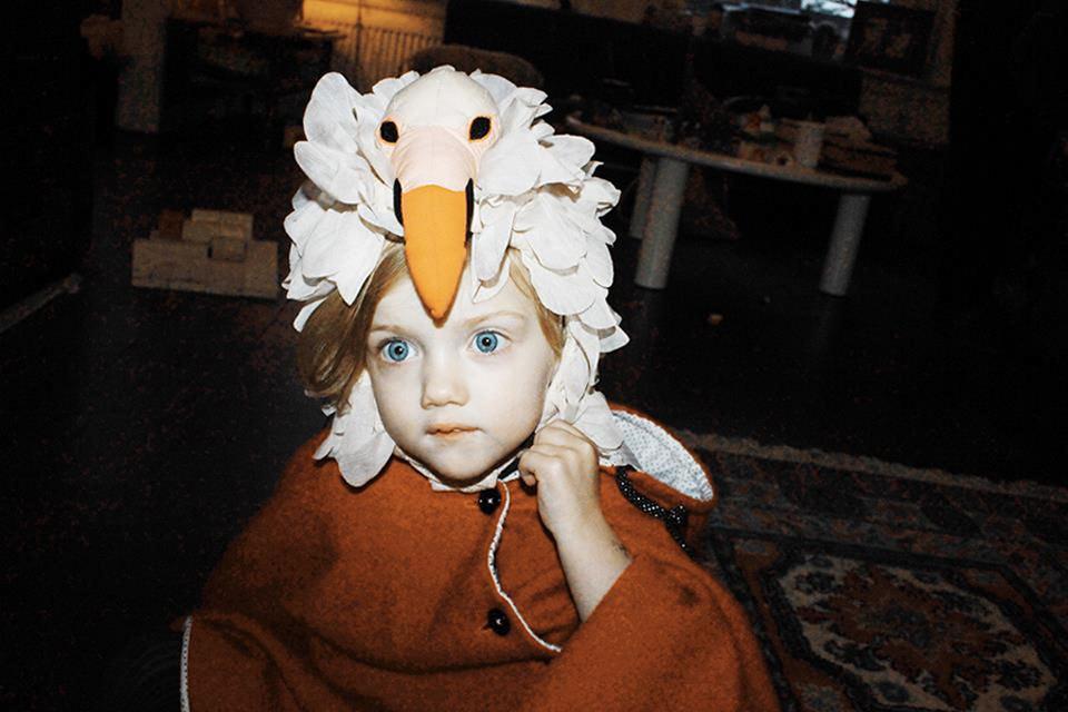 Ein Mädchen mit einem Vogelhut auf dem Kopf.