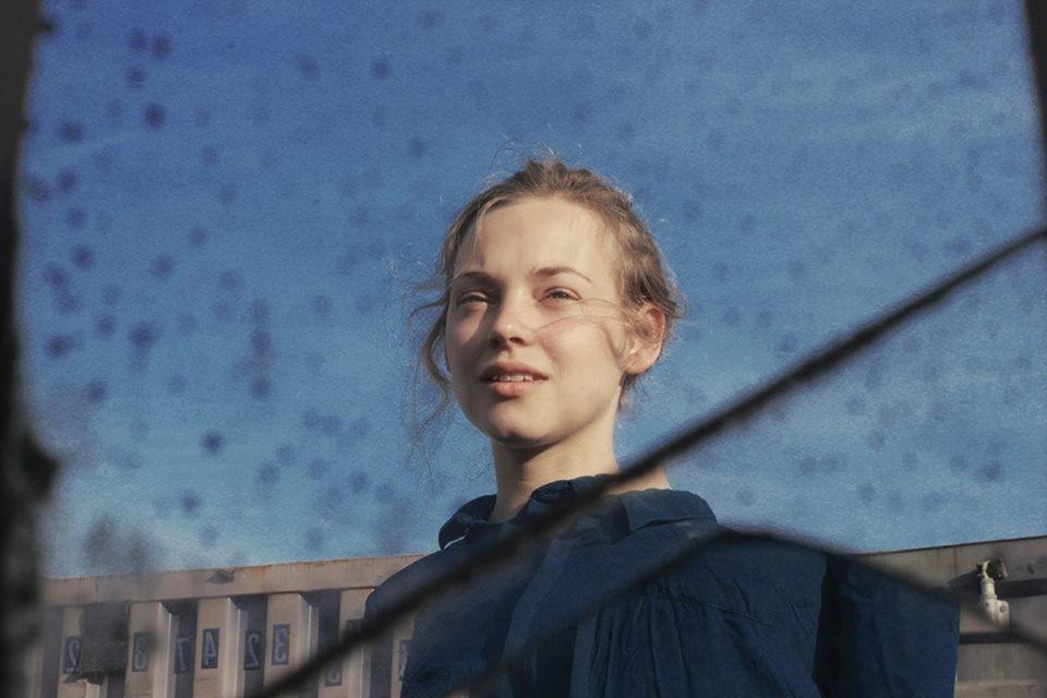 Ein junges Mädchen vor blauem Hintergrund.