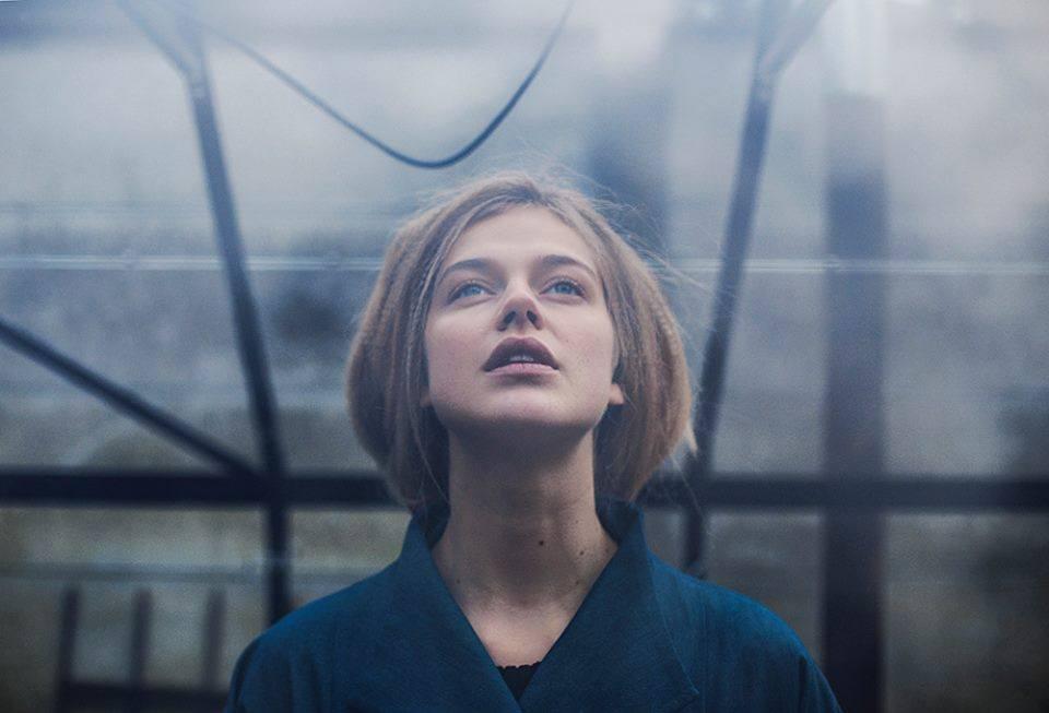 Eine junge Frau schaut nach oben.