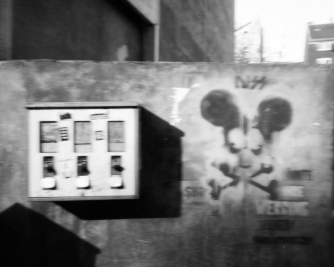 Graffiti Maus und Kaugummiautomat an einer Wand.