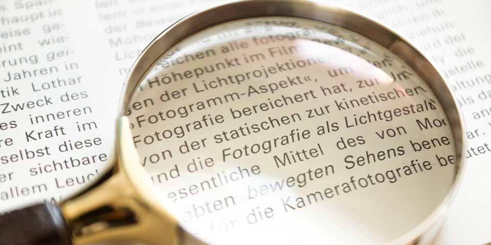 """Lupe, die auf einem Buch liegt und das Wort """"Fotografie"""" vergrößert"""