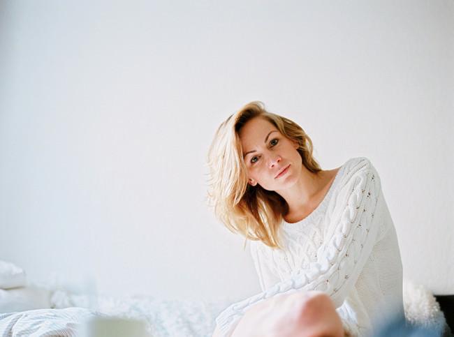 Eine Frau in weißem Pullover sitzt auf einem Bett.