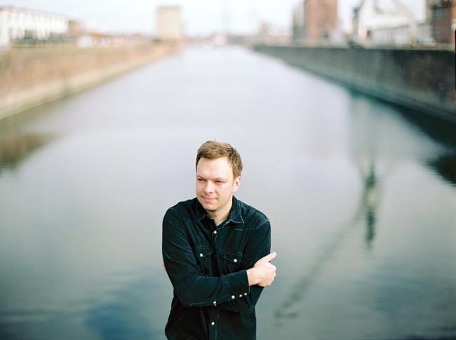 Ein Mann mit verschränkten Armen über einem Fluss.