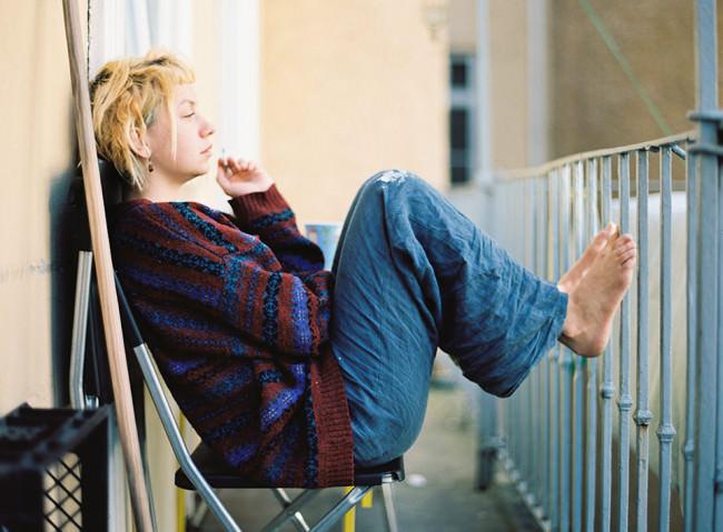 Eine Frau sitzt auf einem Balkon.
