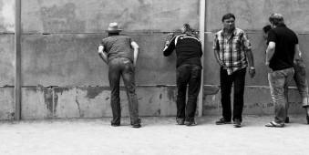 Männer an einer Mauer