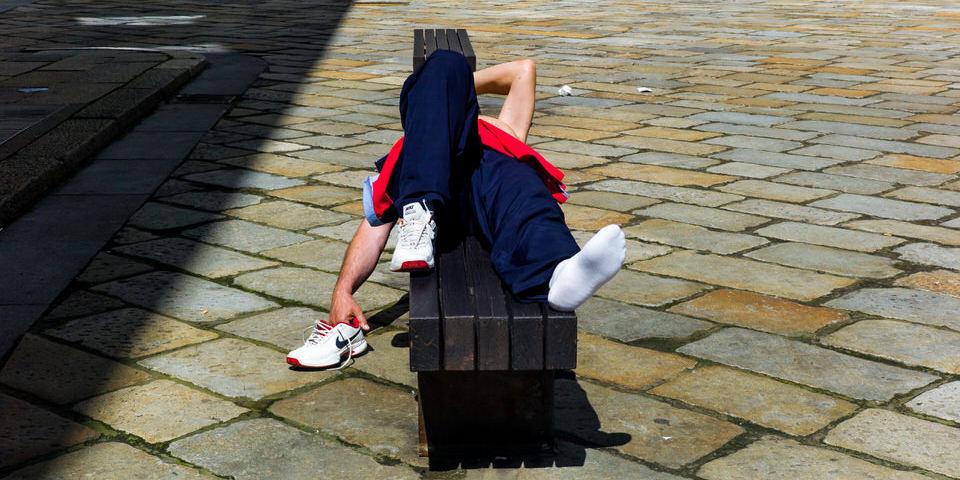 Straßenfotografie: Ein Mann liegt auf einer Bank und sonnt sich.