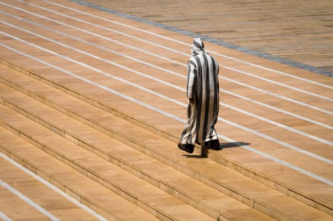 Straßenfotografie: ein Mann mit Streifengewand läuft eine Treppe herab.