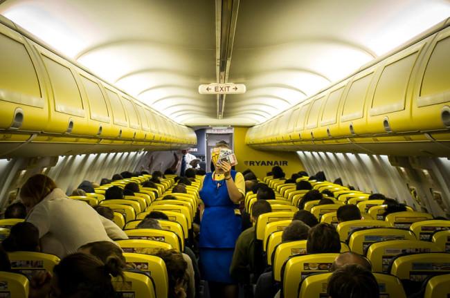 Eine Stewardesse hält sich ein paar Karten vor das Gesicht.