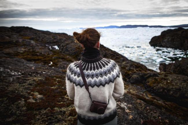 Eine Frau sieht aufs Meer.